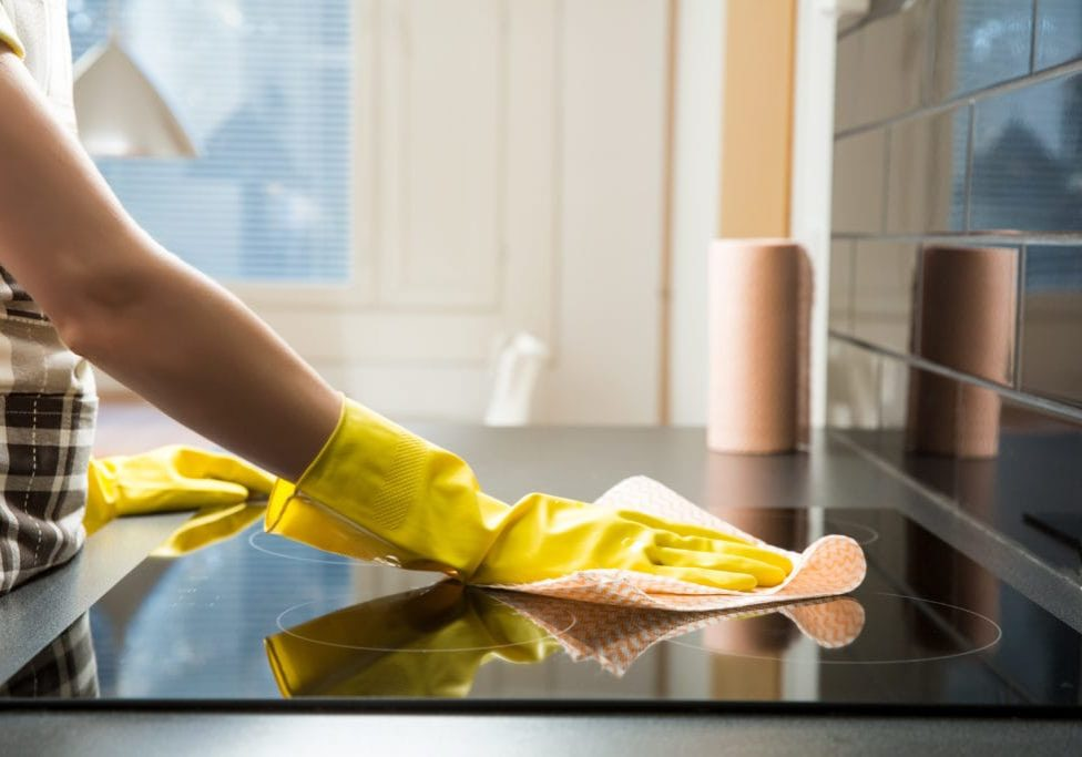 Housewife in rubber protective cleaning and polish electric cooker. Black shiny surface of kitchen top, hands, detergent.